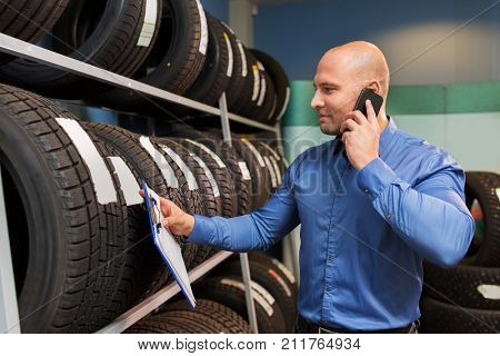 business, maintenance and people concept - male manager with wheel tires and clipboard at car repair service or auto store calling on smartphone