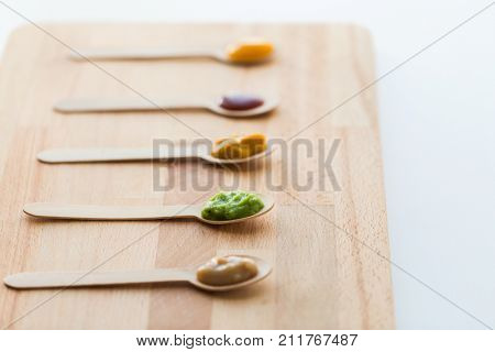 baby food, healthy eating and nutrition concept - vegetable or fruit puree in wooden spoons