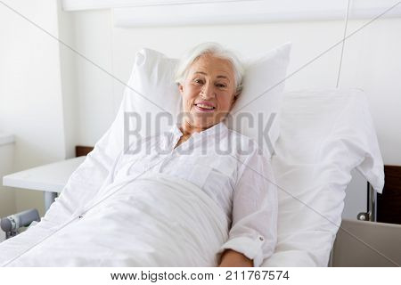 medicine, healthcare and old people concept - smiling senior woman lying on bed at hospital ward
