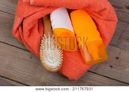 Set Of Bathing Accessories - Orange Towel, Hairbrush And Cosmetics For Pampering On Brown Wooden Bac