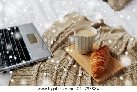 cosy home, interior and winter concept - cozy bedroom with laptop computer, coffee cup and croissant on bed at home over snow