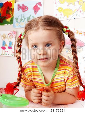Child with piece of chalk draw  in playroom. Preschool.