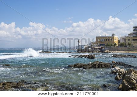 Coastline in Tyre at the ocean with waves and with lighthouse at a sunny day with blue skyin Tyre, Sour, Lebanon