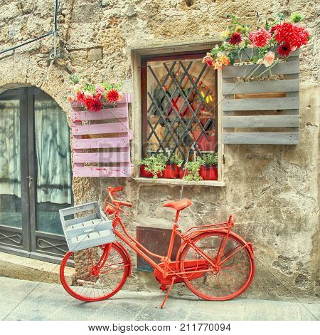 Red bike standing in front of old stone wall in a traditional Italian medieval town, Tuscany, Italy. Square toned image