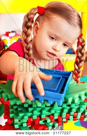 Child with puzzle, block and construction set in playroom. Preschool.