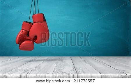 3d rendering of two red boxing gloves hanging above a wooden desk in front of a blue blackboard background. Boxing match. Fighting equipment. Professional sport.