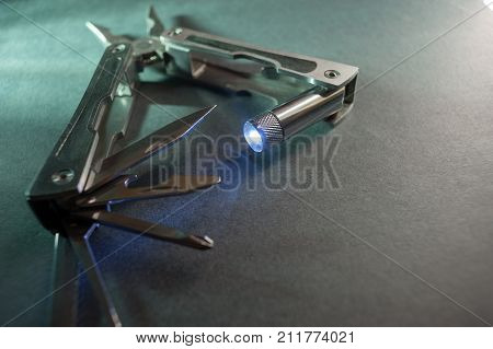 Combined pliers, multifunctional, with flashlight. Against the background of a gray texture.