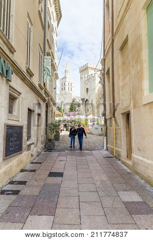 AVIGNON, FRANCE - APRIL 2, 2017: Narrow city street with Pope`s Palace in the background, Avignon, Southern France