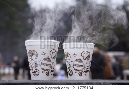 Two cups of hot tea in the cold. Steam rises from the cups with a hot drink. The picture was taken at the city festival winter.