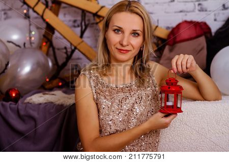 Portrait of a beautiful woman holding on hand red retro style glowing lantern over magical Christmas fairytale