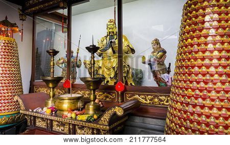 Shanghai, China - Nov 6, 2016: In the 600-year-old Old City God Temple. General Guan Yu's (patron Taoist deity) statue is in a glass cabinet, showing him reading a book. Some reflections observed.