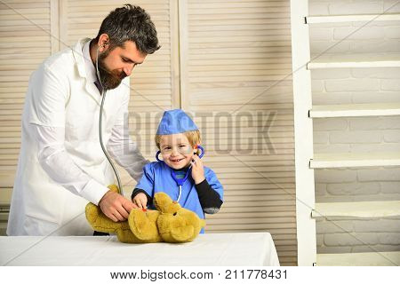 Man with beard and boy hold stethoscope on wooden background. Health and childhood concept. Father and kid with happy faces play doctor. Pediatrician and assistant examine teddy bear poster