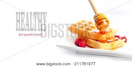 Waffles with honey and berries close-up. Healthy breakfast. Honey pouring on a fresh Belgian waffles.