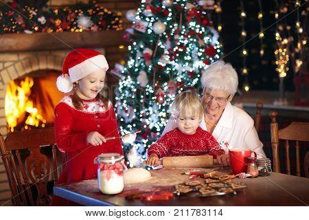 Grandmother And Kids Bake Christmas Cookies.