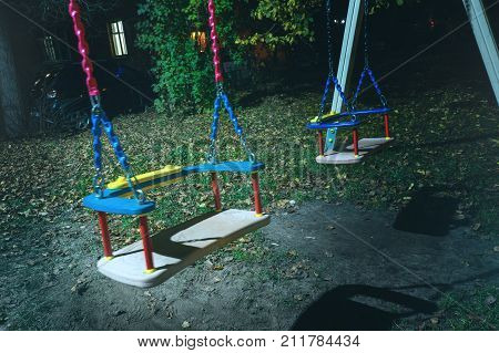 empty children's swing in the street at night the concept of the end of childhood the sadness of loneliness