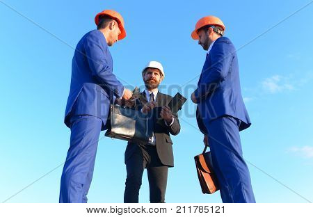 Engineers Hold Meeting On Blue Sky Background. Coworking And Construction