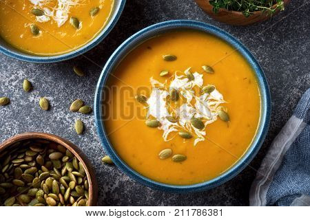 Delicious creamy homemade pumpkin soup with cream and pumpkin seed garnish.