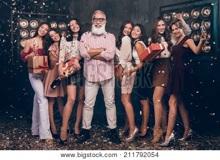Christmas happy party! New Year 2018! Group of attractive girls and happy modern and fashion Santa. Party with gifts and champagne. People dancing in gold confetti and give gifts