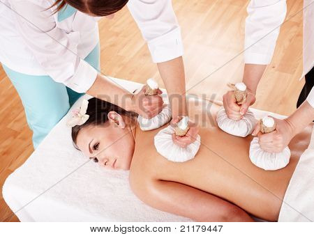 Girl  having Thai herb compress massage in beauty spa. Body care.