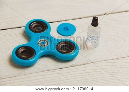 Blue fidget spinner stress relieving toy on white wooden background