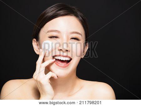 happy woman applying lotion cream on face