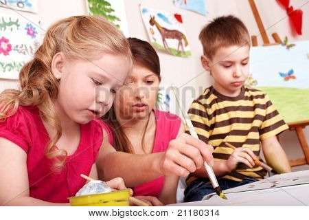 Children painting with teacher in play room.