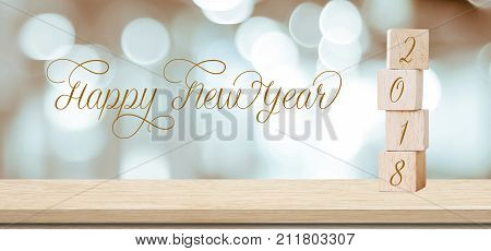Wooden cubes with 2018 and happy new year over blur bokeh background banner with copy space for text new year greeting card template
