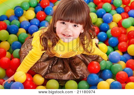 Happy little girl in group colourful ball.
