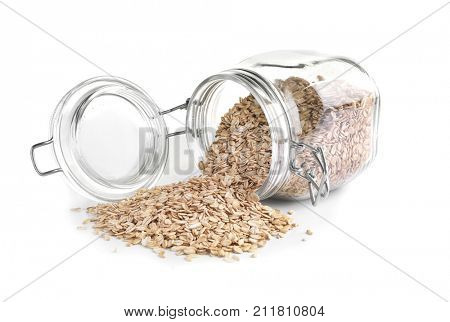 Overturned glass jar with raw oatmeal on white background
