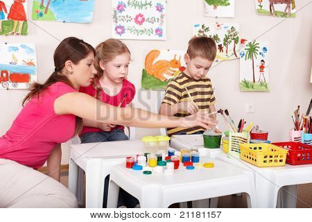 Children painting with teacher in art class. Child care.