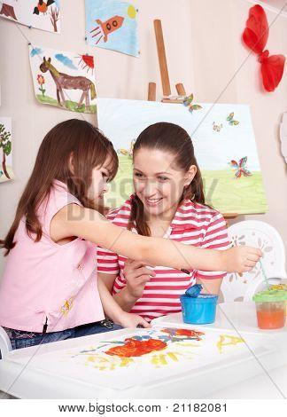 Klein meisje schilderen met moeder thuis.