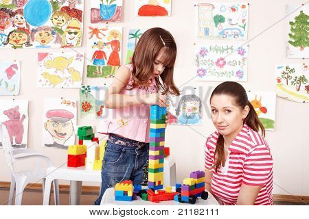 Little girl playing construction set with mother.