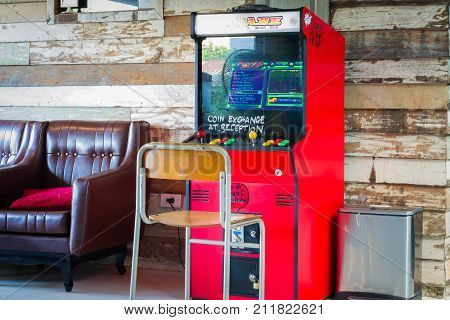 BANGKOK THAILAND - OCTOBER 19: retro red game coin console or Vintage arcade machine at wooden wall background on October 19 2017 in Bangkok Thailand.