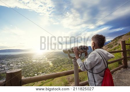 Young boy looking out through binoculars at the mountain view of the city down below after hiking up a mountain trail.