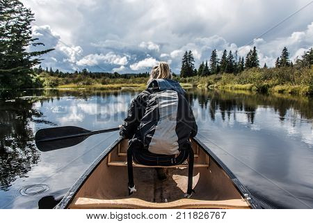 Girl canoeing with Canoe on the lake of two rivers in the algonquin national park in ontario Canada on a sunny cloudy day