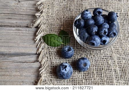 Fresh organic blueberries in a glass bowl on old wooden background.Blueberry. Bilberries.Healthy eating,vegan food,diet and nutrition concept.