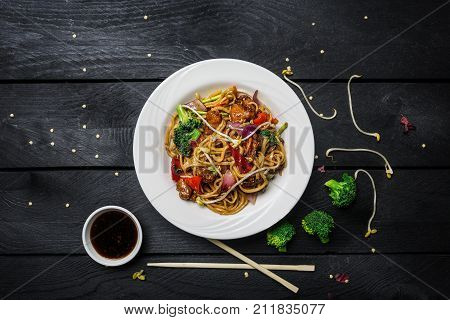Udon stir fry noodles with chicken and vegetables in a white plate on black wooden background. With chopsticks and sauce. Top view.