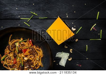 Udon stir fry noodles with meat and vegetables in wok pan on black wooden background. With a box for noodles Top view.
