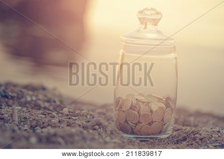 Investment passive income and saving concept. Coins in a glass jar on the beach in rays of the sun