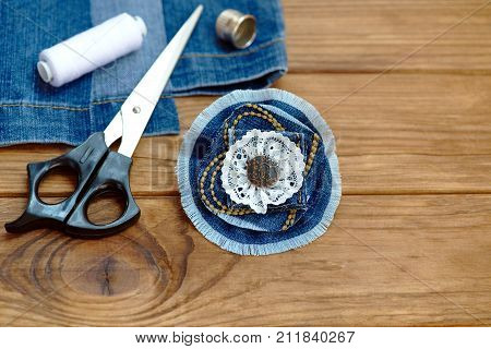 Craft idea for old jeans. Handicraft denim flower brooch. Scissors, thread, thimble, needle, female old jeans on a wooden background. How to use old jeans to make a flower brooch. Closeup