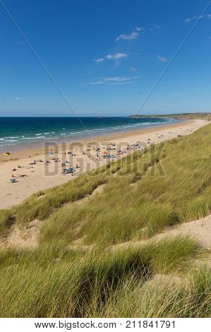 St Ives Bay beach Cornwall uk in summer with people blue sky and sea, view towards Godrevy lighthouse