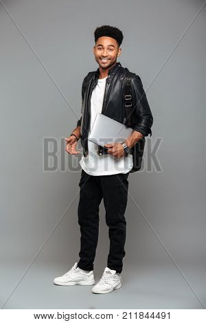 Full length portrait of a smiling young african man in leather jacket holding laptop computer while standing and looking at camera isolated over gray background