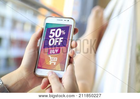 Woman in a hammock with a smartphone with a 50% discount advertising on the screen.  Marketing, ecommerce, discount, email marketing, cell phone publicity.