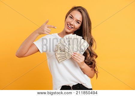 Portrait of a happy cheerful girl pointing finger at bunch of money banknotes isolated over yellow background