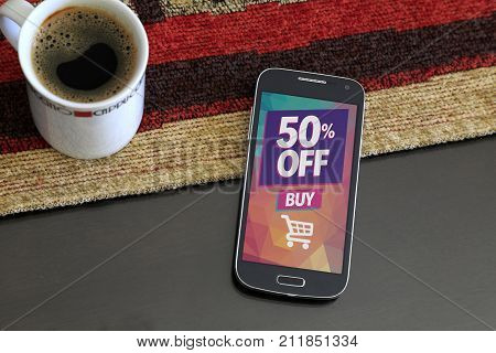 Smartphone with a 50% discount advertising on the screen. Beside a cup of coffee. Marketing, ecommerce, discount, internet publicity.