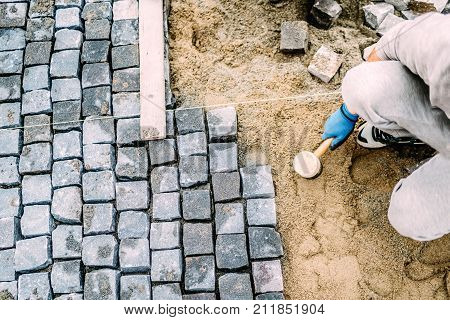 Manual Labor, Industrial Worker Laying Stone Pavement On Sand Path