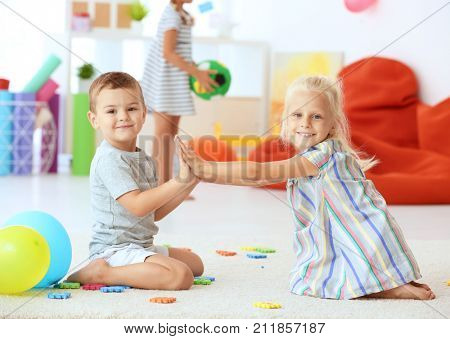 Cute children playing a clapping game indoor