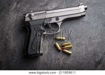 9mm pistol bullets and handgun on black table.