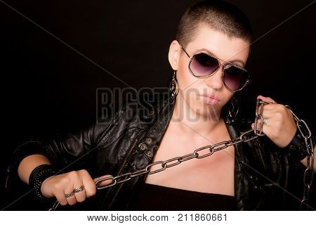 Fashion hard rock bald woman in black glasses and leather coat with metal chain posing on black background