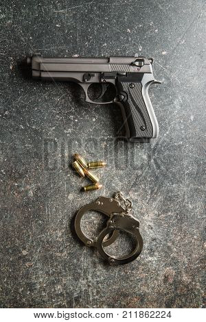Pistol bullets, handgun and handcuffs on black table.